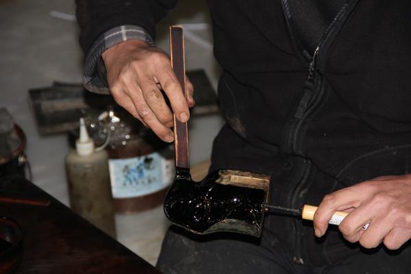 須弥壇の高欄(須弥壇の端にある手すり)の一部分に漆を塗る職人